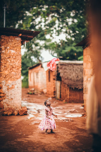 Africa Building Exterior Built Structure Child Children Girls Lifestyles Outdoors Palm Trees Playing Red Soil Road Rural Travelling Travelphotography Vacation Village Worn Out Zanzibar