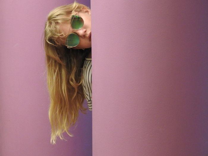 Portrait of girl in sunglasses peeking behind wall