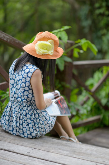 Rear view of woman reading magazine at park