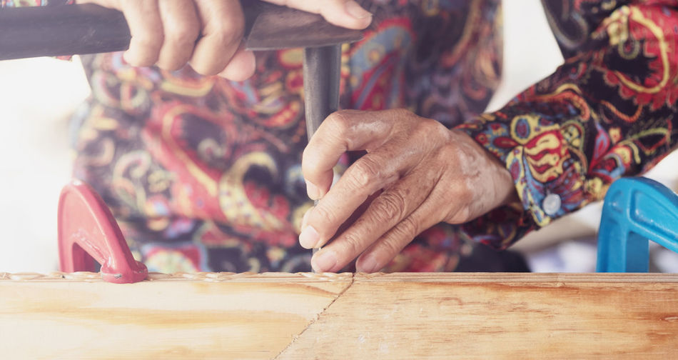 Midsection of person working on wood