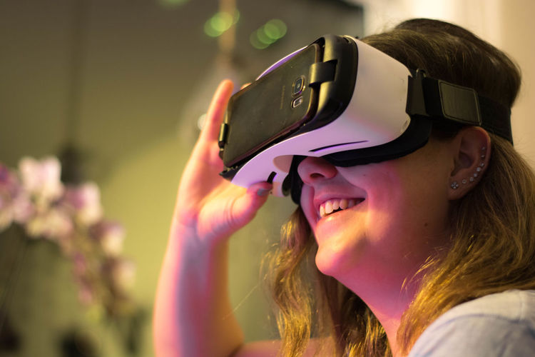 Happy woman wearing virtual reality simulator in illuminated room