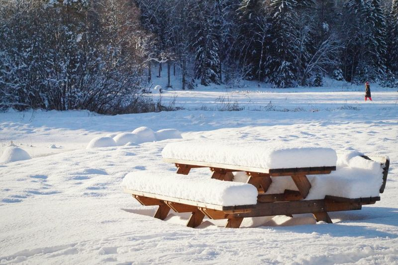 Snow Covered Wooden Picnic Table On Field