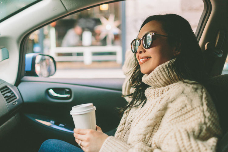 EyeEmNewHere Beautiful People Beautiful Woman Car Car Interior Coffee - Drink Coffee Cup Day Eyeglasses  Happiness Land Vehicle Lifestyles Mode Of Transport One Person One Young Woman Only Outdoors Portrait Real People Sitting Smiling Sunglasses Transportation Warm Clothing Women Young Adult Young Women