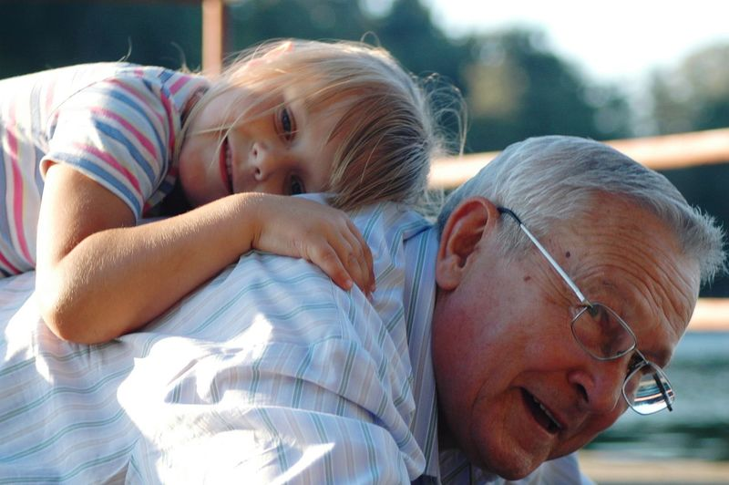 Grandfather Carrying Granddaughter On Back