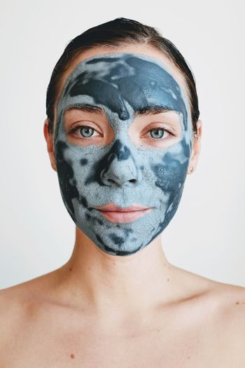 Portrait of young woman with facial mask against white background