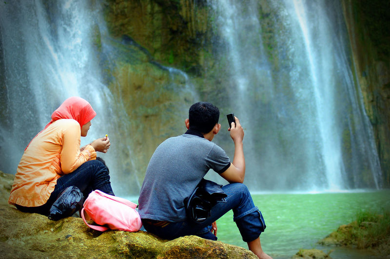 Rear view of people sitting against waterfall