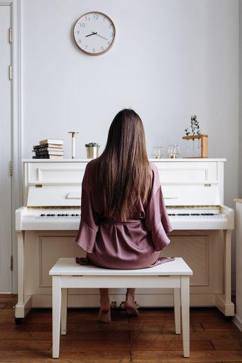A beautiful woman playing the white piano