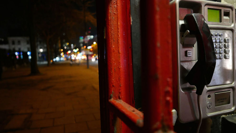 Pay phone in booth at night