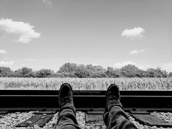 Low section of man sitting on railroad track