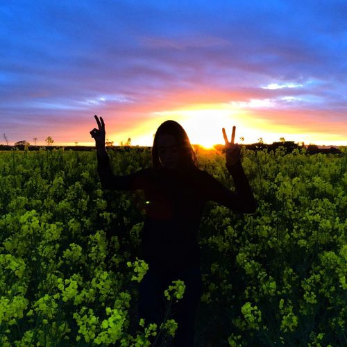 Woman standing in field against dramatic sky