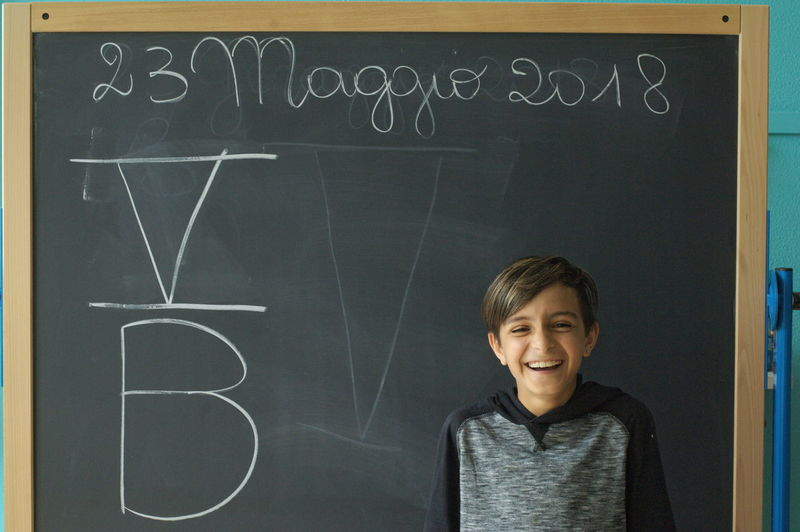 Cheerful Boy Standing Against Blackboard In Classroom