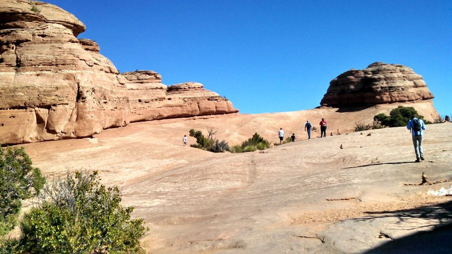 People against rock formations at arches national park