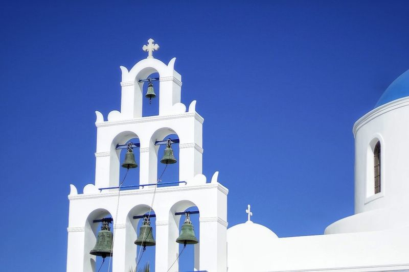 Oia Santorini, Greece Religion Place Of Worship Architecture Travel Destinations Bell Outdoors No People Building Exterior Sky Clear Sky Vacations Summer Day Modern Abandoned City Cross Low Angle View Architectural Column Spirituality First Eyeem Photo Built Structure Streetphotography