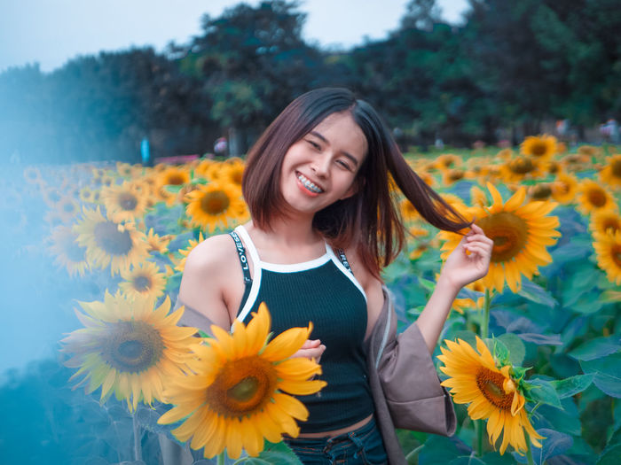 Portrait Of Smiling Young Woman Standing On Sunflower Field