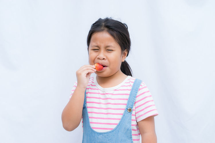 Cute Girl Eating Strawberry Against White Background