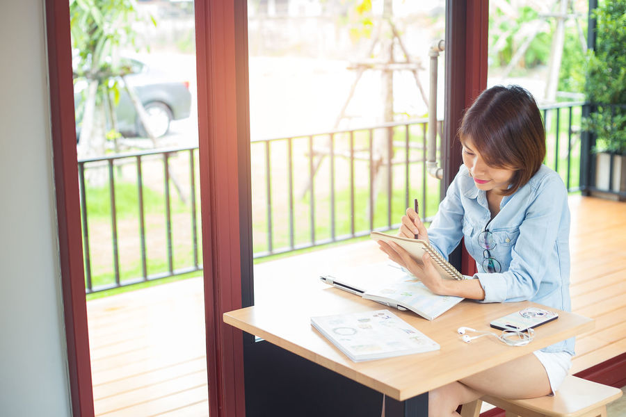 Young woman was reading and take note in a notebook ASIA Reading Woman Working Adult Casual Clothing Day Hairstyle Indoors  Lifestyles Looking One Person Sitting Studying Table Take Note Window Wireless Technology
