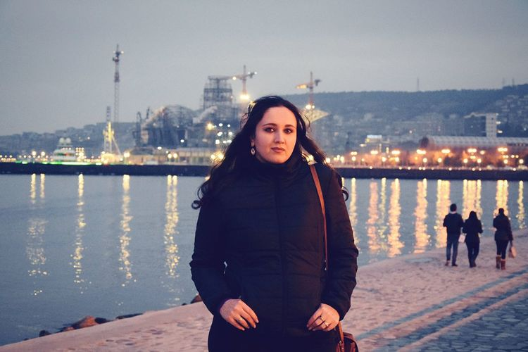 Portrait of young woman standing by lake on walkway in city at dusk