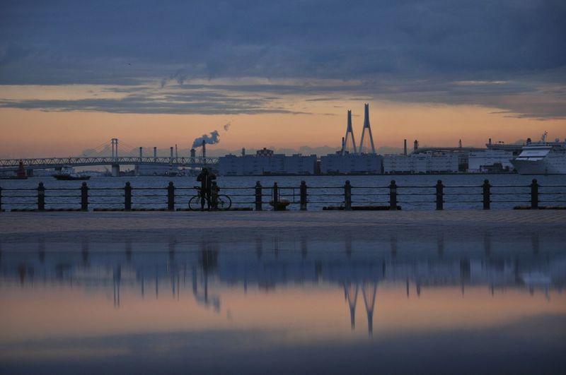 Yokohama bay bridge over sea against cloudy sky during sunrise