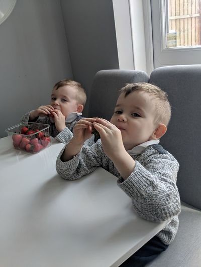 Brothers eating strawberries while sitting at home