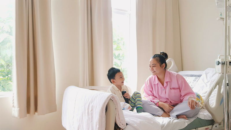 Hospital Hospital Bed Windows Sunlight Focus On Foreground Toddler  Kid Boy Woman Mother And Son Eyeemphoto Sitting On Bed Showcase June Laughing Happy Family Family Portrait Cheer Smile Healthcare Medical Care Festival Season Ill Health Medical Treatment