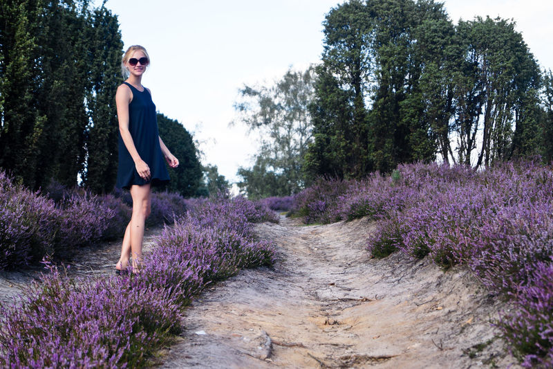 Full length of woman standing amidst lavender flowers on field