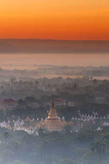 Beautiful scenery during of sunset of top view at Mandalay hill in Myanmar ASIA Mandalay Hill Architecture Beauty In Nature Belief Building Building Exterior Built Structure Fog Mist Myanmar Nature No People Orange Color Outdoors Pagoda Building Place Of Worship Religion Scenics - Nature Sky Spirituality Sunrise Sunset Tranquility Travel Destinations