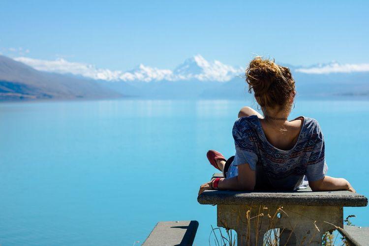 Rear view of woman looking at lake during summer