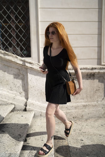 Full length of young woman on staircase