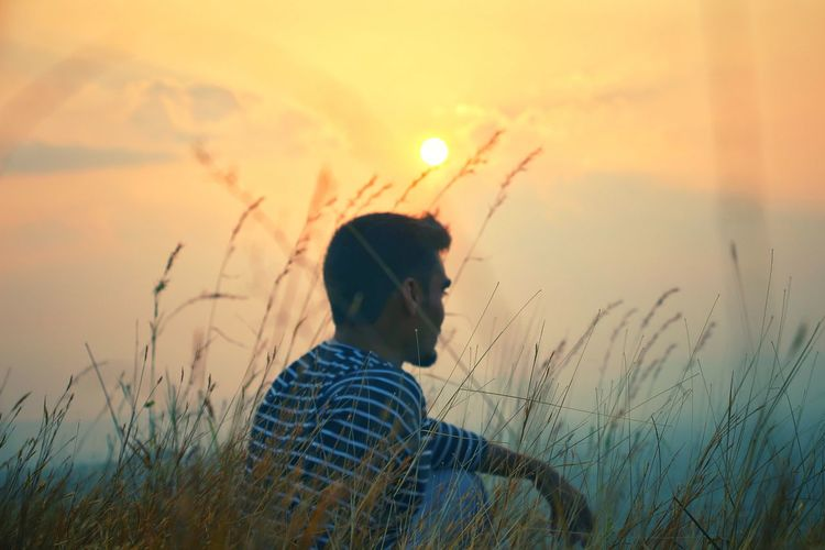 Side view of man sitting on field against sky during sunset