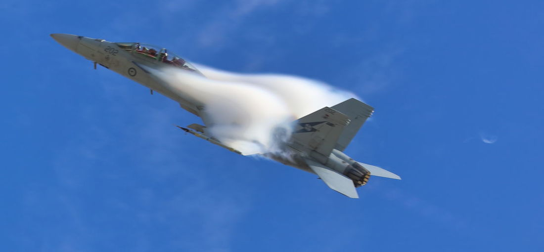 An Australian F18 fighter jet pulling a 8.5G sharp turn, causing the air to compress over the top of its wings. Air Vapor Airshow Blue Close-up Day EyeEmNewHere F18 Super Hornet Fighter Jet Fighter Plane Flying Jet Fighter Low Angle View Military Motion Outdoors Sky