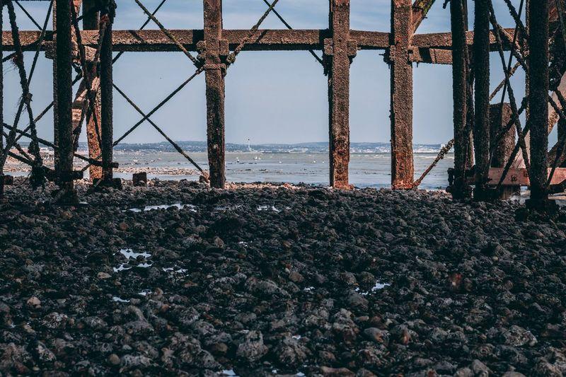 Rusty metallic structure on beach against sky