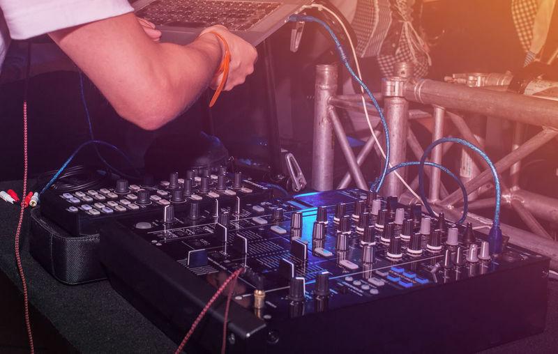 Club Dj Holding Laptop Over Sound Mixer At Nightclub