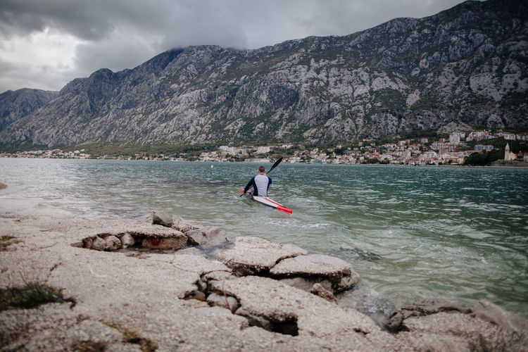 man kayaking in mountain bay. Montenegro, Kotor bay Kayaking Man Adult Adventure Bay Beauty In Nature Beauty In Nature Day Extreme Sports Kayak Leisure Activity Male Mountain Mountain Range Nature One Person Outdoors People Real People Rock - Object Sea Sky Sport Water Water Sports