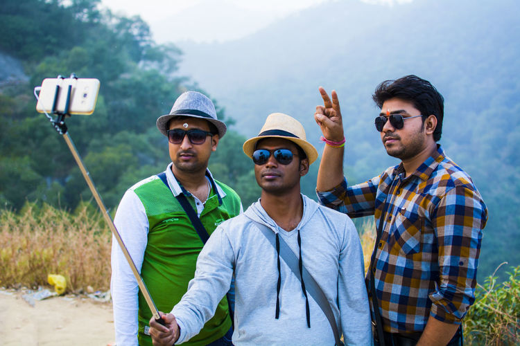 Male friends taking selfie with monopod against mountain