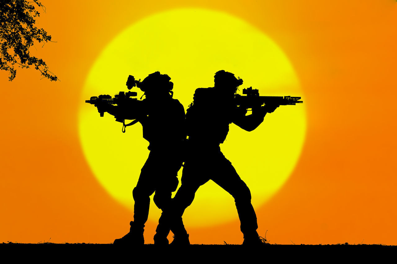 SILHOUETTE MEN ON FIELD DURING SUNSET