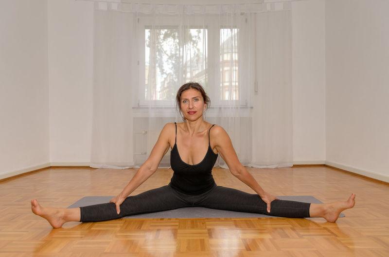 Portrait of young woman sitting on hardwood floor