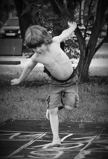Shirtless boy playing hopscotch at park
