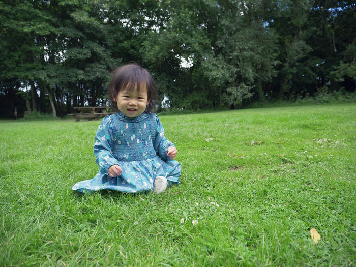 Asian Baby Girl Bangs Childhood Cute Day Full Length Garden Grass Happiness Looking At Camera Nature One Person Outdoors People Playing Field Portrait Sitting Smiling Smiling Face Tree