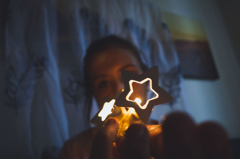 Close-up of woman holding star shape sitting in darkroom
