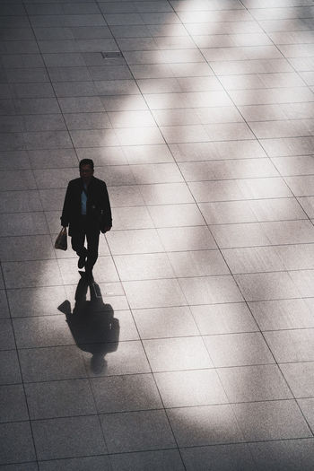 Full Length Men Walking One Person Business Person High Angle View Businessman Well-dressed Formalwear Suit Indoors  Flooring Business Day Real People Briefcase Males  Tile Bag Tiled Floor