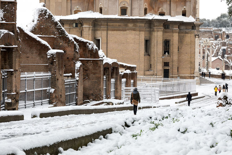 Snow covers the streets of Rome, Italy. Ancient Roman road, Clivus Argentarius Animal Themes Architecture Building Exterior Built Structure Cold Temperature Day Mammal Nature One Person Outdoors People Real People Snow Snowing Walking Warm Clothing Weather Winter