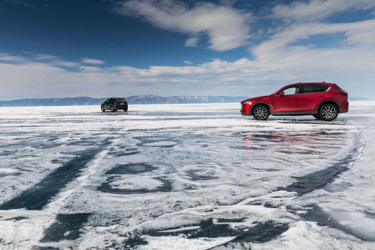 Car on snow covered field against sky