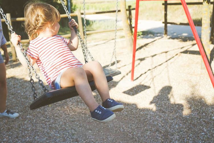 Child Childhood One Person Shadow Real People Full Length Sunlight Casual Clothing Day Lifestyles Rear View Females Women Leisure Activity Girls Nature Sitting Playground Outdoors Innocence Hairstyle