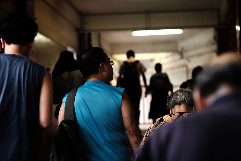 Rear view of people standing in corridor