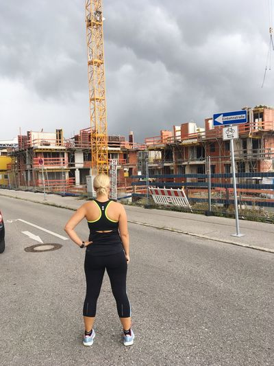 Full length of woman with arms outstretched against sky in city