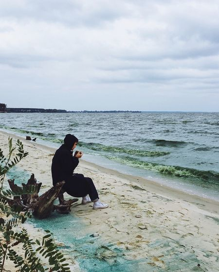 Man sitting on beach against sky