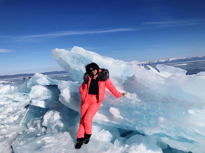 Portrait of woman standing by ice against sky
