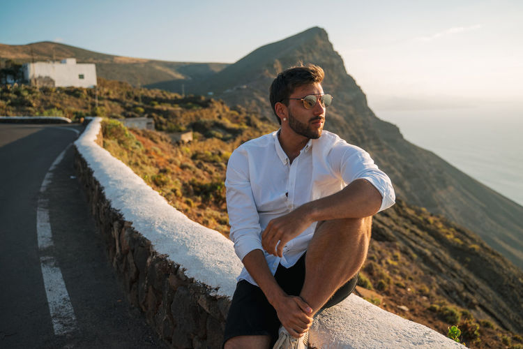 Young man wearing sunglasses sitting on mountain against sky