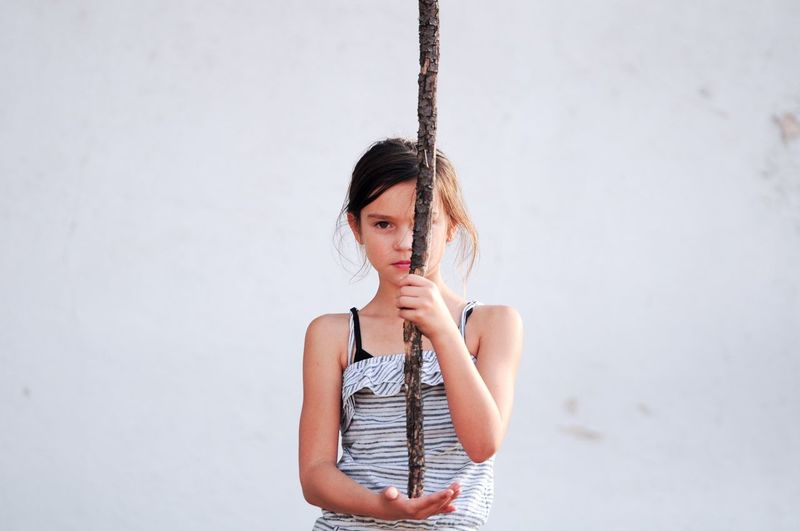 Portrait of girl holding stick while standing against wall