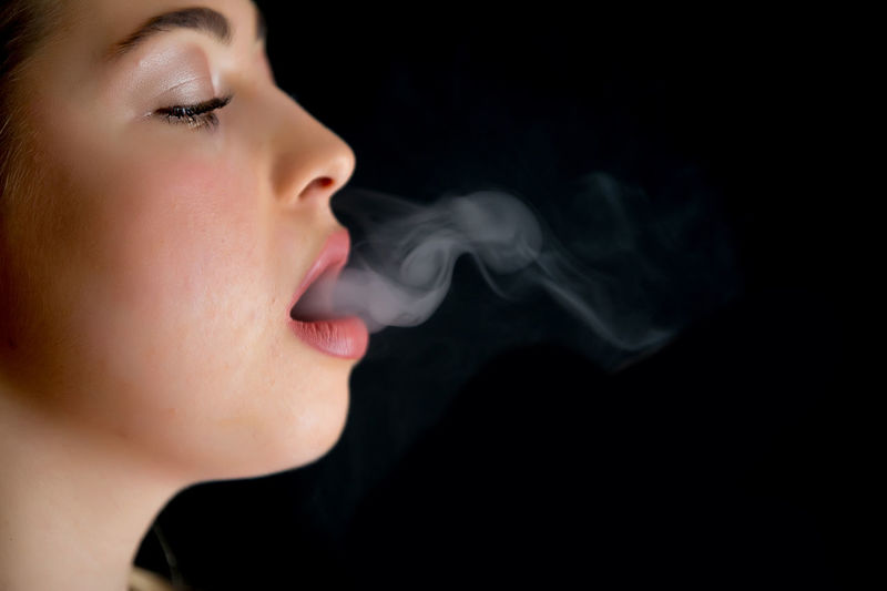 Close-up of woman smoking over black background